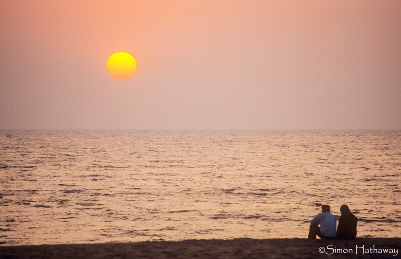 A couple enjoy the sunset off the Keralan coast, India.. Image shot 01/2007. Exact date unknown.